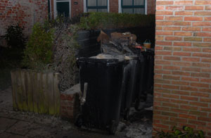 Containers tegen woning in brand