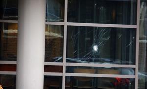 Man slaat acht ruiten politiebureau in