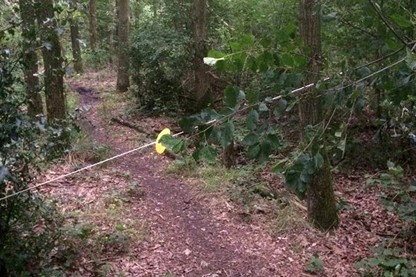 Mountainbikers boos om gespannen touw in bos