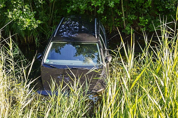 Auto rolt water in na vergeten handrem